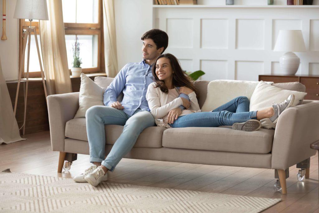 Junges Pärchen sitz innig auf dem Sofa ihre Wohnzimmers