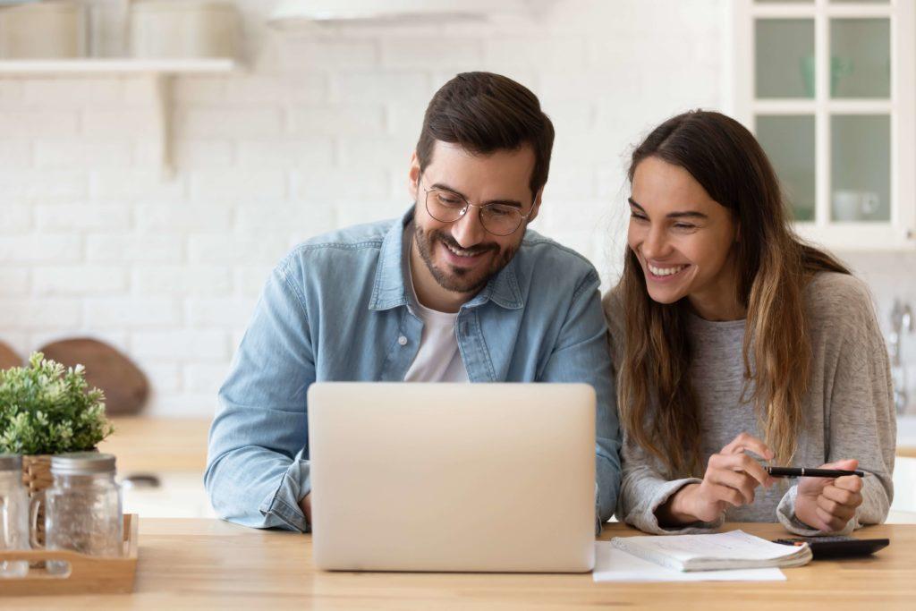 Junges Paar sitzen mit Taschenrechner und Papieren vor dem Laptop