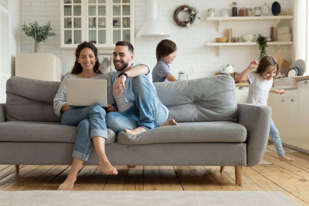 Junge Eltern sitzen mit dem Laptop auf dem Sofa. Die Kinder rennen um das Sofa herum