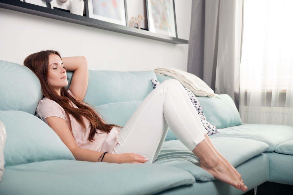 Junge Frau sitz entspannt auf dem Sofa